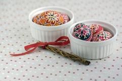 在白色碗的五颜六色的被绘的复活节彩蛋在被加点的桌布,传统美丽的复活节静物画 免版税图库摄影