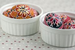 在白色碗的五颜六色的被绘的复活节彩蛋在被加点的桌布,传统美丽的复活节静物画 库存图片