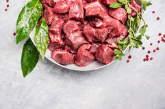 在白色碗的切好的未加工的牛肉肉用在轻的木背景的新鲜的草本 图库摄影