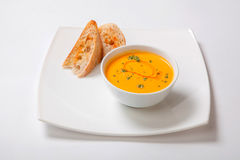 在白色碗的南瓜奶油色汤有切片的白面包 免版税库存图片