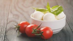 在白色碗的小无盐干酪球用李子西红柿 图库摄影