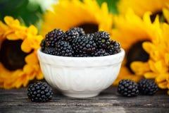 在白色碗的成熟黑莓有在木桌,夏天题材上的向日葵花束的 图库摄影