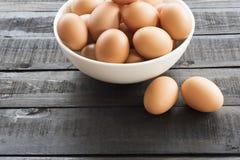 在白色碗的新鲜的鸡蛋和2鸡蛋在黑colo支持 免版税库存照片