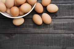 在白色碗的新鲜的鸡蛋和6鸡蛋在黑colo支持 免版税库存图片
