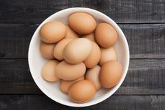 在白色碗的新鲜的鸡蛋在黑颜色木头桌上 库存图片