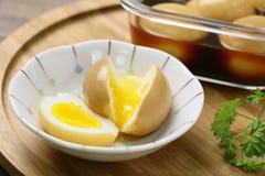在白色碗的流动的鸡蛋用在木桌上的被炖的鸡蛋 免版税库存照片