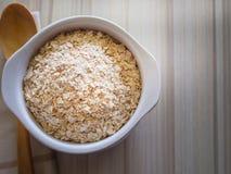 在白色碗的燕麦米在顶面桌木蠕虫口气图象 免版税库存照片