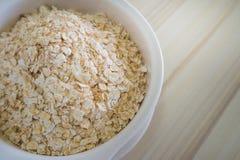在白色碗的燕麦米在顶面桌木蠕虫口气图象 免版税图库摄影