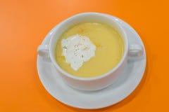 在白色碗的玉米汤在橙色背景 免版税库存照片