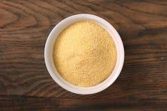 在白色碗的玉米粉麦片粥在黑褐色木背景 库存照片