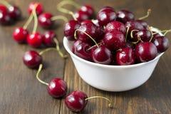 在白色碗的甜成熟樱桃在桌上 免版税库存图片