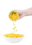在白色碗的甜玉米准备好为吃用手和匙子 免版税库存图片