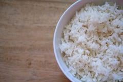在白色碗的米在木桌上 库存图片