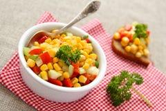 在白色碗的自创玉米辣调味汁有匙子的 免版税库存照片