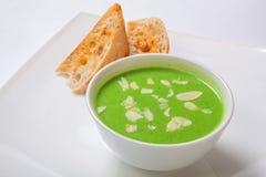 在白色碗的芦笋奶油色汤用面包 免版税库存图片