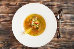 在白色碗的蔬菜汤在木土气桌上 顶视图 图库摄影