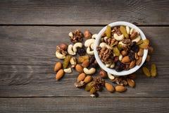在白色碗的被分类的坚果在木桌上 库存照片
