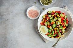 在白色碗的鲕梨、黑豆、玉米和甜椒沙拉 库存照片
