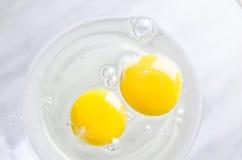在白色碗的鸡蛋在厨房用桌上 图库摄影