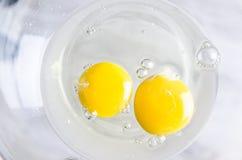 在白色碗的鸡蛋在厨房用桌上 库存照片