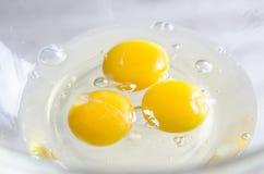 在白色碗的鸡蛋在厨房用桌上 免版税库存图片
