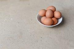 在白色碗的鸡蛋在水泥地板上 免版税图库摄影