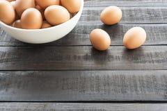 在白色碗的鸡鸡蛋和3只鸡鸡蛋在黑co支持 库存照片