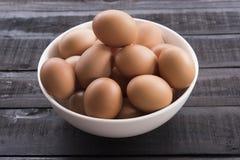 在白色碗的鸡鸡蛋在黑颜色木头桌上 库存照片