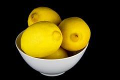 在白色碗的整个柠檬在黑背景 免版税库存图片
