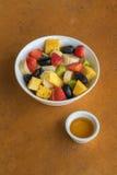 在白色碗的水果沙拉在橙色石背景 图库摄影