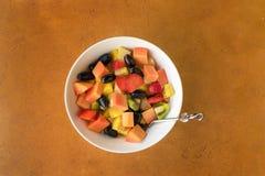 在白色碗的水果沙拉在石背景 顶视图 图库摄影