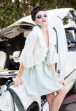 在白色礼服、佩带蓝色构成摆在的毛皮和高脚跟的美好的妇女模型室外 库存图片