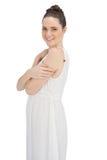 在白色礼服摆在的快乐的年轻模型 免版税库存照片