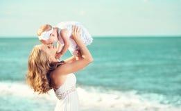 在白色礼服的愉快的家庭 母亲投掷天空的婴孩 免版税库存照片