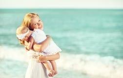 在白色礼服的愉快的家庭 母亲拥抱天空的婴孩 免版税库存照片