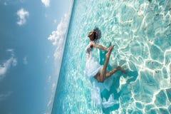 在白色礼服的美丽的女性画象在海洋 免版税库存图片