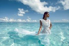 在白色礼服的美丽的女性画象在海洋 库存图片