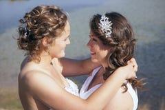 在白色礼服的结婚的愉快的女同性恋的夫妇在小湖附近 库存图片