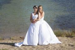 在白色礼服的结婚的愉快的女同性恋的夫妇在sm附近拥抱 图库摄影