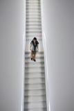 在白色立方体画廊的人下降的楼梯 免版税库存图片