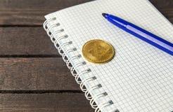 在白色笔记本和bitcoin放置的标志 免版税图库摄影