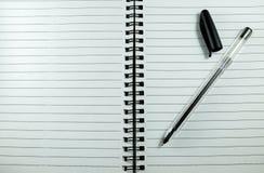 在白色笔记本的黑笔 免版税图库摄影