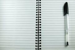在白色笔记本的黑笔 库存照片