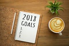 在白色笔记薄的2018个目标与在木桌上的咖啡拿铁 库存照片