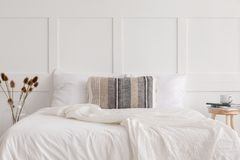 在白色简单的卧室内部,真正的照片的加长型的床 免版税库存照片