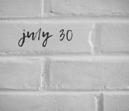 在白色简单的砖墙30日写的7月 免版税库存图片