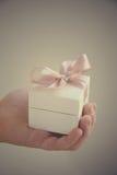 在白色箱子的一件礼物有一把桃红色弓的 免版税图库摄影