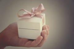 在白色箱子的一件礼物有一把桃红色弓的 图库摄影