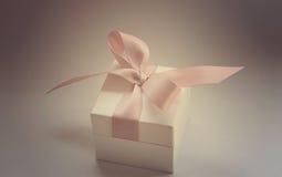 在白色箱子的一件礼物有一把桃红色弓的 库存图片