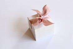 在白色箱子的一件礼物有一把桃红色弓的 库存照片